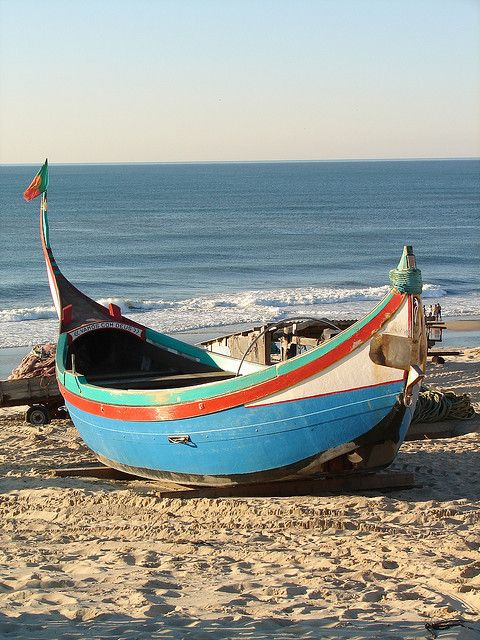 Nazarre, Portugal fishing boats. Fish were drying on racks, and women wearing 7 layers of petticoats sitting on the beach were mending nets.