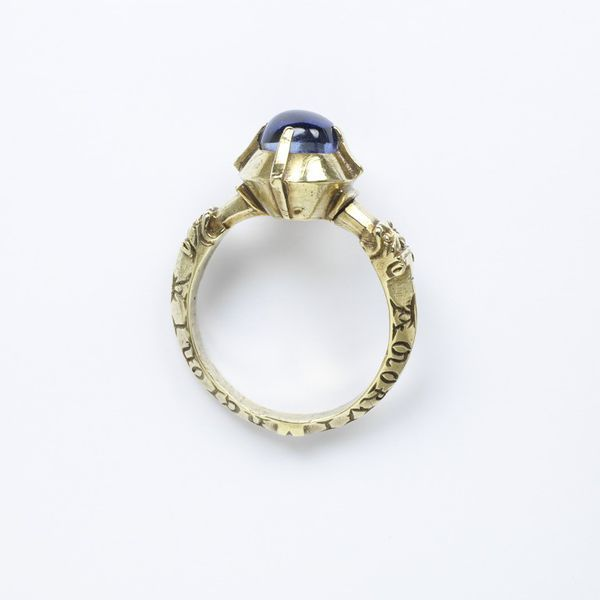 Gold ring, 1300-1400, Europe, the projecting four-claw bezel set with a polished cabochon sapphire, the hoop with lion-mask shoulders. The hoop inscribed in Lombardic lettering AVE MARIA GRA[CIA] (Hail Mary Full of Grace) and AMOR VINCI[T] O[M]NIA (Love Conquers All).