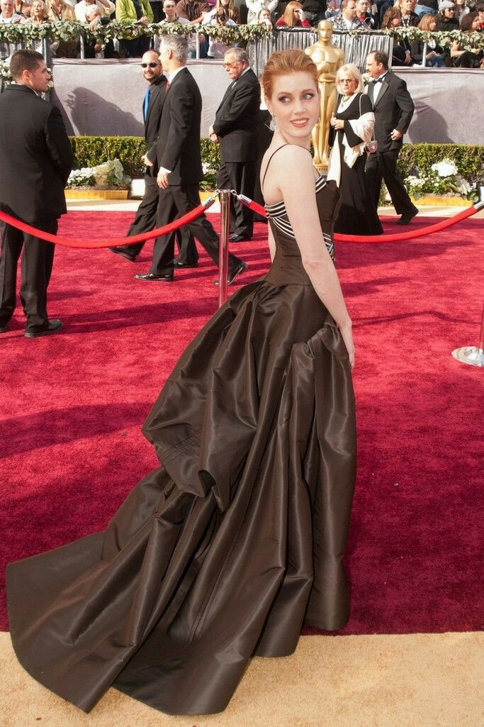 74. What a stunner! First timer Amy Adams in a dramatic, brown satin creation by Carolina Herrera  at the 2006 Oscars Red Carpet.