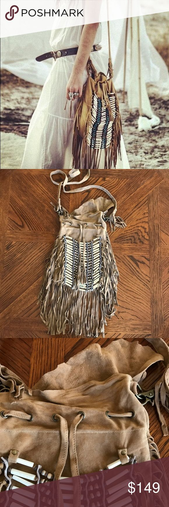 """New Free People Spell And Gypsy Dreamweaver Bag Leather crossbody bag with leather fringe trimming and drawstring closure at top. Tiered bead embellishment on the front. Long leather strap. Leather is super soft and supple. Inside is lined with one pocket.  Please note the bag's right hinge will not open so the strap can not be removed. Please see photos.  NWOT. This bag was purchased at the manufacturer's outlet center.  The bag's body measures approximately 8"""" by 11"""" not including the…"""