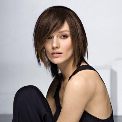 Cette jeune femme aux cheveux mi-longs a opté pour une jolie coupe au carré inégal, et son coiffeur a effilé les pointes. Il a aussi tracé une raie sur un côté et a fait descendre une longue frange qui traverse le front en camouflant un oeil.