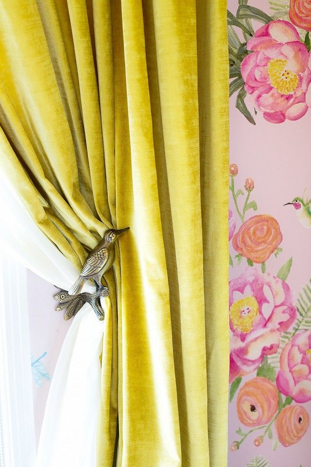 Nursery with custom wallpaper, yellow curtains, and a detailed bird curtail pull