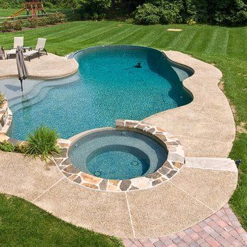 Beautiful pool with faux edge, sun shelf with umbrella, and raised stone coping spa with | Yelp