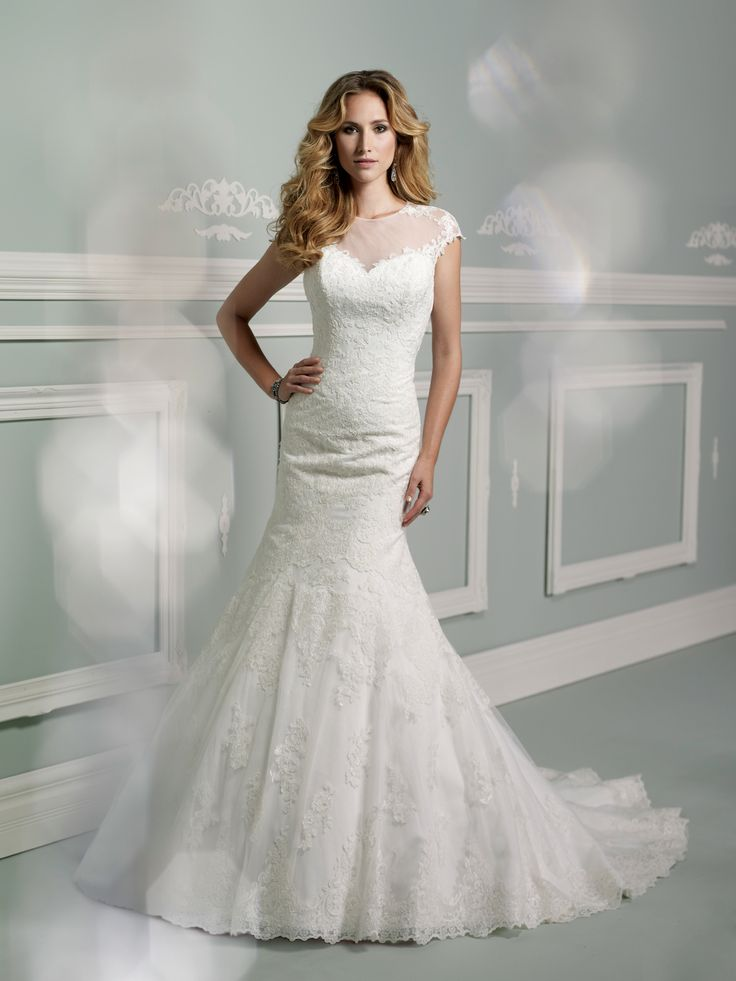 Lace, tulle and point d'Esprit mermaid gown, cap sleeves with lace trim, illusion jeweled neckline with striking open back lace bodice with covered button closure, low dipped back adorned with covered buttons, sweetheart bodice features embroidered lace extending down to dramatic dropped waistline, point d'esprit skirt features matching lace appliqués and scalloped hemline, chapel length [...]