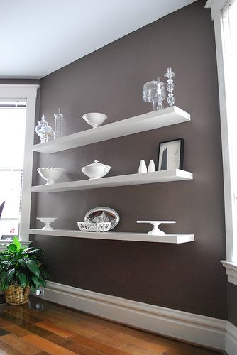 i love the dark wall with the white shelves. good for displays someday. dining room wall shelves. white with glass or silver accents.