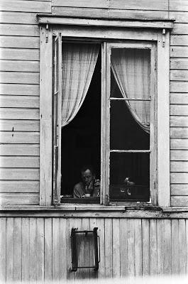 Mies ajamassa partaansa puutalon avoimen ikkunan ääressä Hertankadulla Länsi-Pasilassa. 1970
