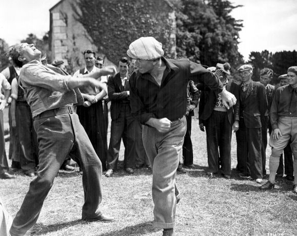 John Wayne dukes it out with Victor McLaglen in The Quiet Man. The Quiet Man, one of John Ford's many iconic movies, explored the desire to return to Ireland and attempt to fit in with an insular society. It made a huge star of Maureen O'Hara and further cemented John Wayne's stature. It also put Ireland on the map as a film making destination.