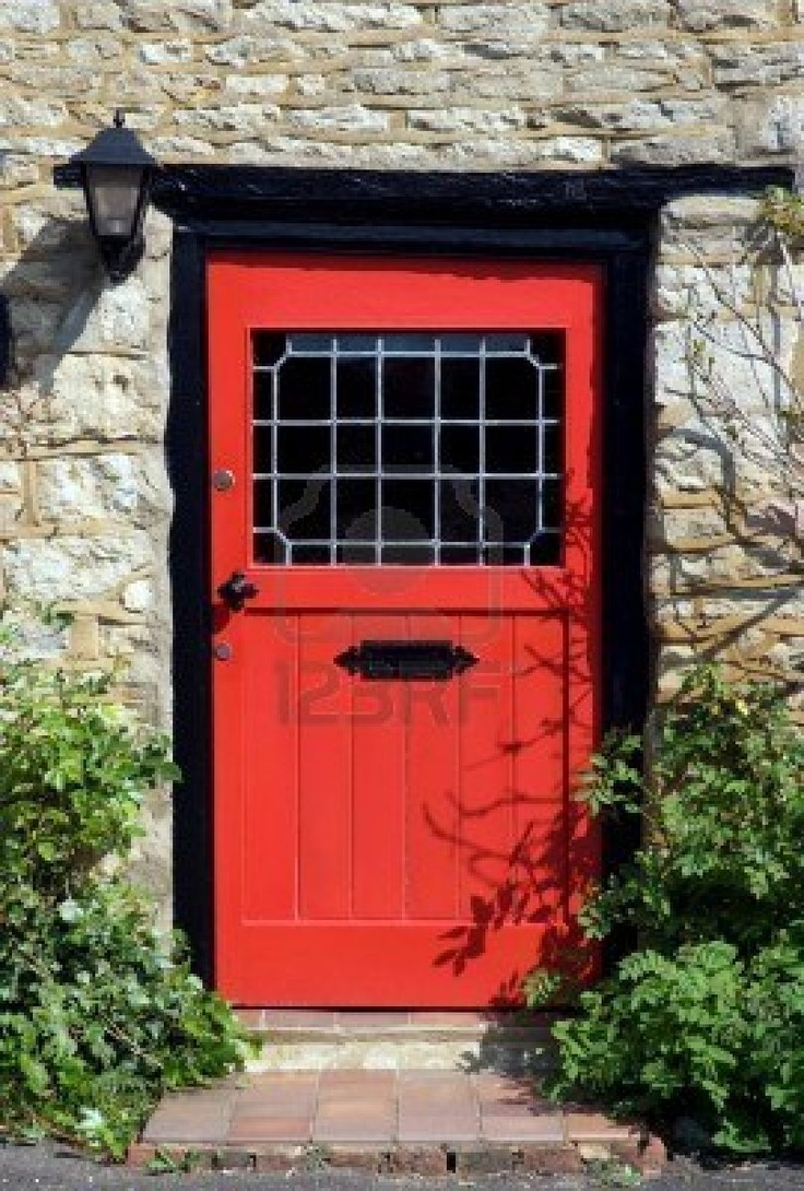 Front door of an old english cottage - An Old Red Door To The Front Of An English Country Cottage Stock Photo