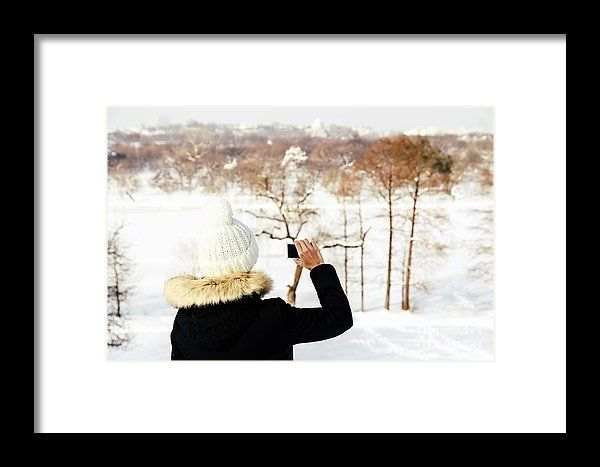 Cute Girl Taking Photos With Mobile Phone In Winter Framed Print