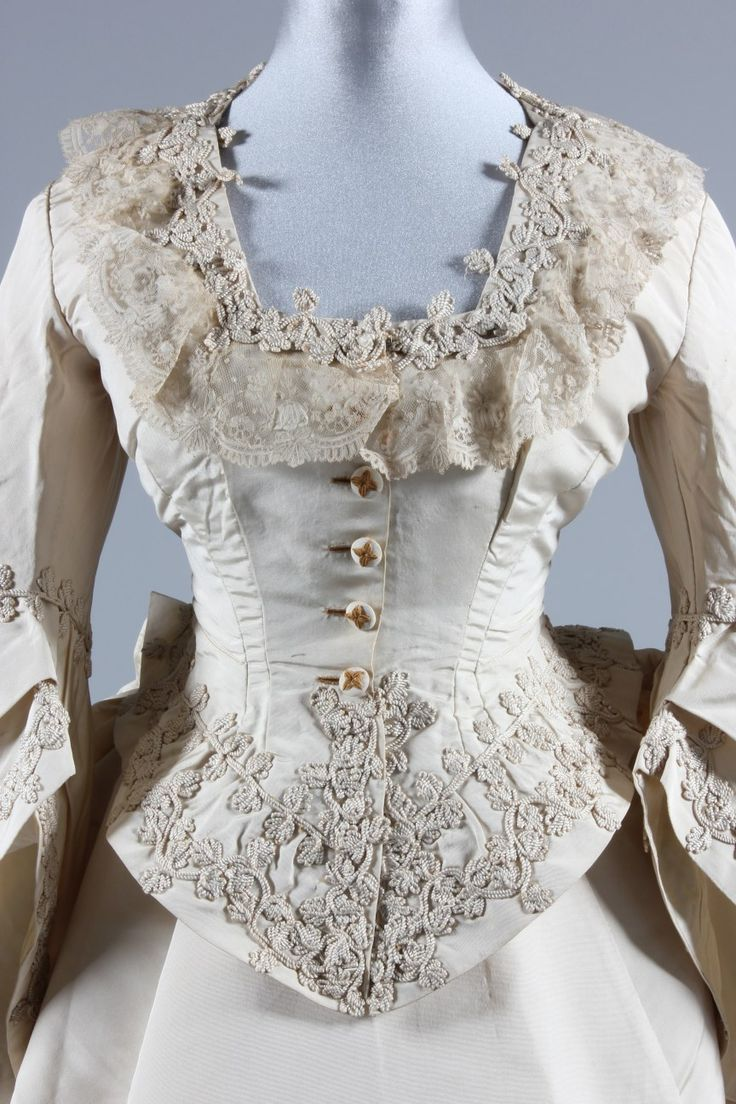 An ivory silk faille bridal gown, circa 1871, the bodice and waistband of skirt applied with 'Grand Magasins de la Paix' stamped labels, the bodice with bell-shaped sleeves, jacket-like bodice with curved basque, adorned with Brussels lace and ivory cord passementerie; the apron-type overskirt similarly adorned, over plain faille trained skirt with integral ruched gathers to the rear in the area to take a bustle. Detail jαɢlαdy