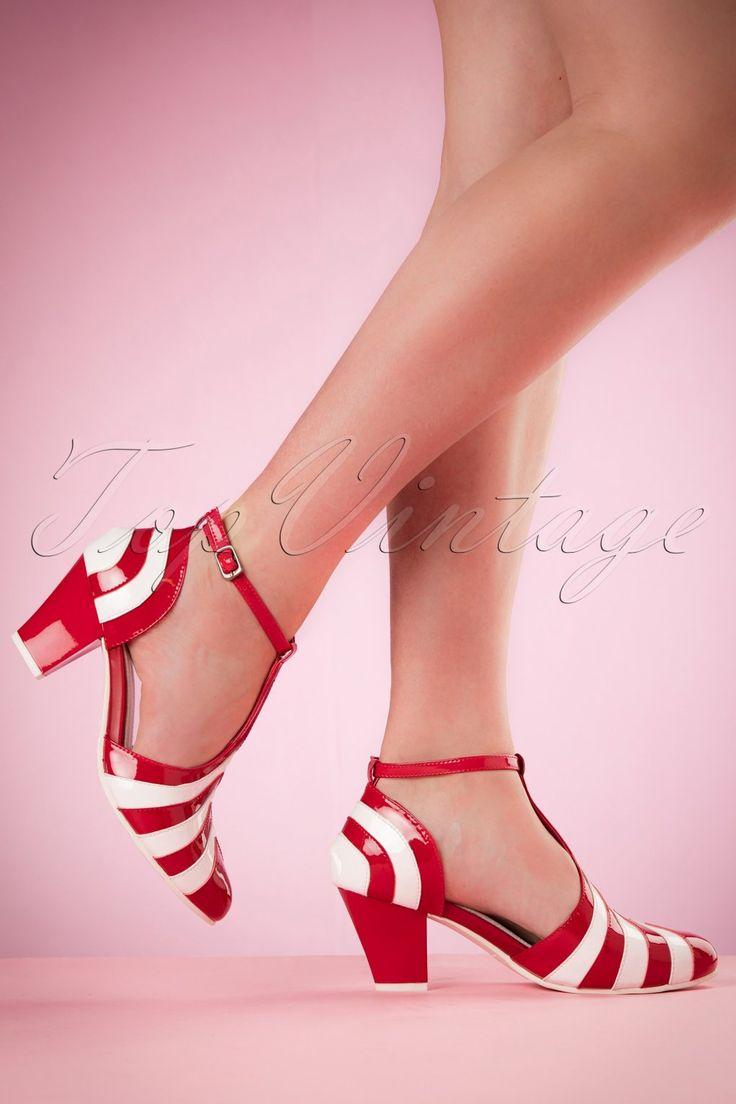 Deze 50s Elsie Striped Patent Pumpszijn prachtige fifties style pumps met pittige details!Wow... deze schatjes zullen je beslist betoveren! Gemaakt van gestreept hoogwaardig lakleer in rood en wit met t-strap. De stevige rode lakleren hak maakt het totaalplaatje compleet. Zodra je ze aan hebt wil je er de hele dag naar kijken, maar denk eraan... tijdens het lopen altijd voor je blijven kijken! ;-)   T-strap Verstelbaar enkelbandje met handige haaksluiting Antiek...