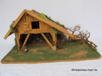 """Alpenländische Krippe. Rustikaler teilweise verfallener Stall. Die Rückwand ist mit Steinen """"gemauert"""" Das Dach mit Schindel gedeckt. Seitlich vom Stall befindet sich in einem kleinen Wald eine Futterkrippe. Vor dem Stall steht ein Karrenrad und ein Baumstammstrahler."""