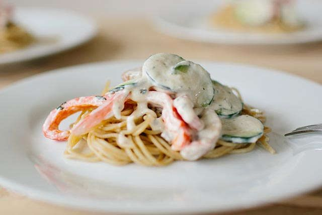 Ce plat coloré est fait de légumes frais cuits dans l'huile d'olive, puis incorporés à une sauce au parmesan et au fromage à la crème, le tout servi sur un lit de spaghettis.