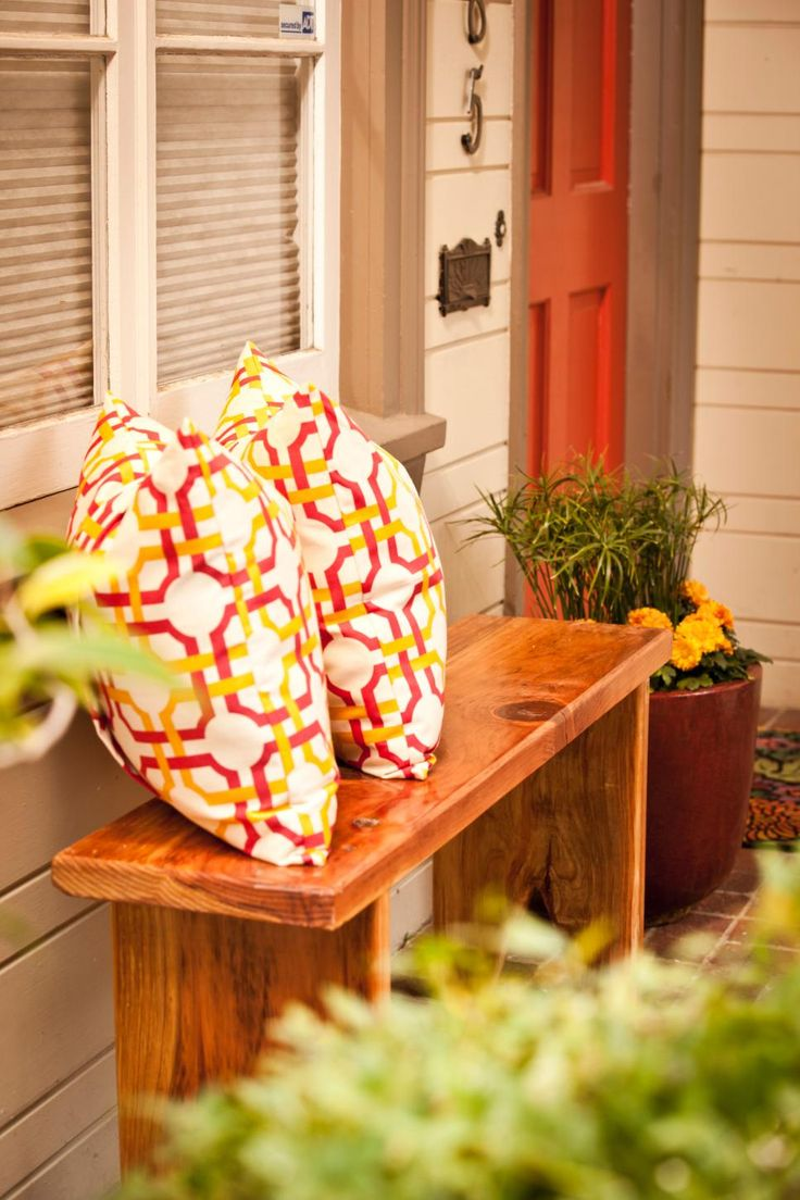 Few things are more welcoming than cozy outdoor living spaces, but too much clutter on the front porch can scare off buyers when you're trying to sell a home. Scale your outdoor furniture to the size of your porch. Here, a small wooden bench adds an inviting touch to this home's entrance without overwhelming the narrow space. The bold pattern in the throw pillows complements the vivid red door.