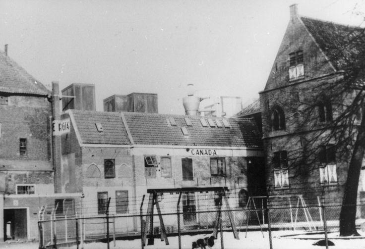 """Gezicht op het Broerenkerkplein met kinderspeelplaats en de Librije. De voederfabriek """"Bergia"""" is nog in vol bedrijf; evenals het pakhuis """"Canada""""."""
