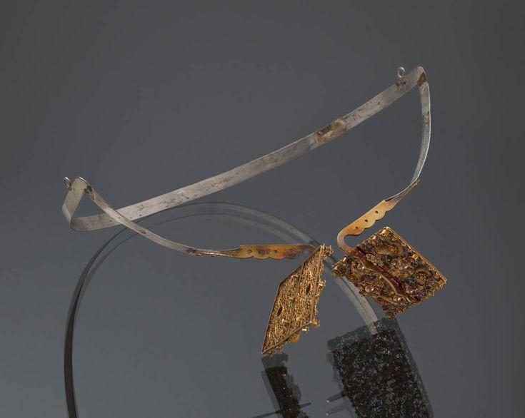 Zilveren oorijzer met 'doorluchtige' (opengewerkte) gouden 'stikken' (oorijzeruiteinden). Gedragen door een vrouw van Zuid-Beveland. Dit is een bijzonder exemplaar. Er zijn maar enkele oorijzers bekend met dergelijke stikken, versierd met filigrein en cantillewerk. Het oorijzer is in 1864 vervaardigd door A.F.A. Wansteeker & Zoon te Amsterdam.