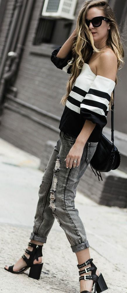 Edgy black and white outfit styled with off the shoulder striped top, grey boyfriend jeans, and buckle sandals