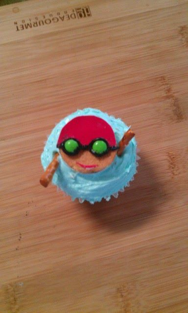Backstroke Swimmer Cupcake by Ana F.    Vanilla wafer, edible paper (swim cap), candy (goggle eyes), black frosting (goggles) and pretzel sticks for the arms