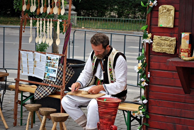 Folklore Festival in Bucharest: in this picture we see an artisan doing some woodwork - traditional wooden spoons, small stools and other carved wooden objects.