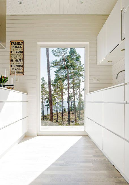 Modern all white Scandinavian kitchen. Note: all storage below counter-top level is made of drawers with no handles.