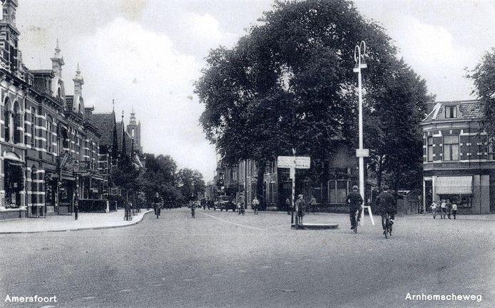 Het Prinses Julianaplein rond 1935. Motorisch verkeer was er nauwelijks. Midden op het plein een hoge lantaarnpaal met daarnaast een minirotonde en een verkeersbord. De fietsers lijken het geen verwarrende situatie te vinden.