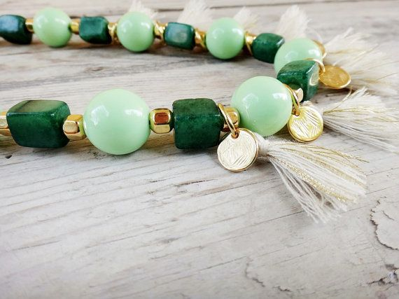 This unique piece is a long beaded handmade boho necklace with jade gemstones, green acrylic beads, freshwater pearls, beige cotton tassels and gold