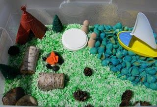 Camping sensory bin!  Green rice, blue shells for water, logs, pine cones, peg people.
