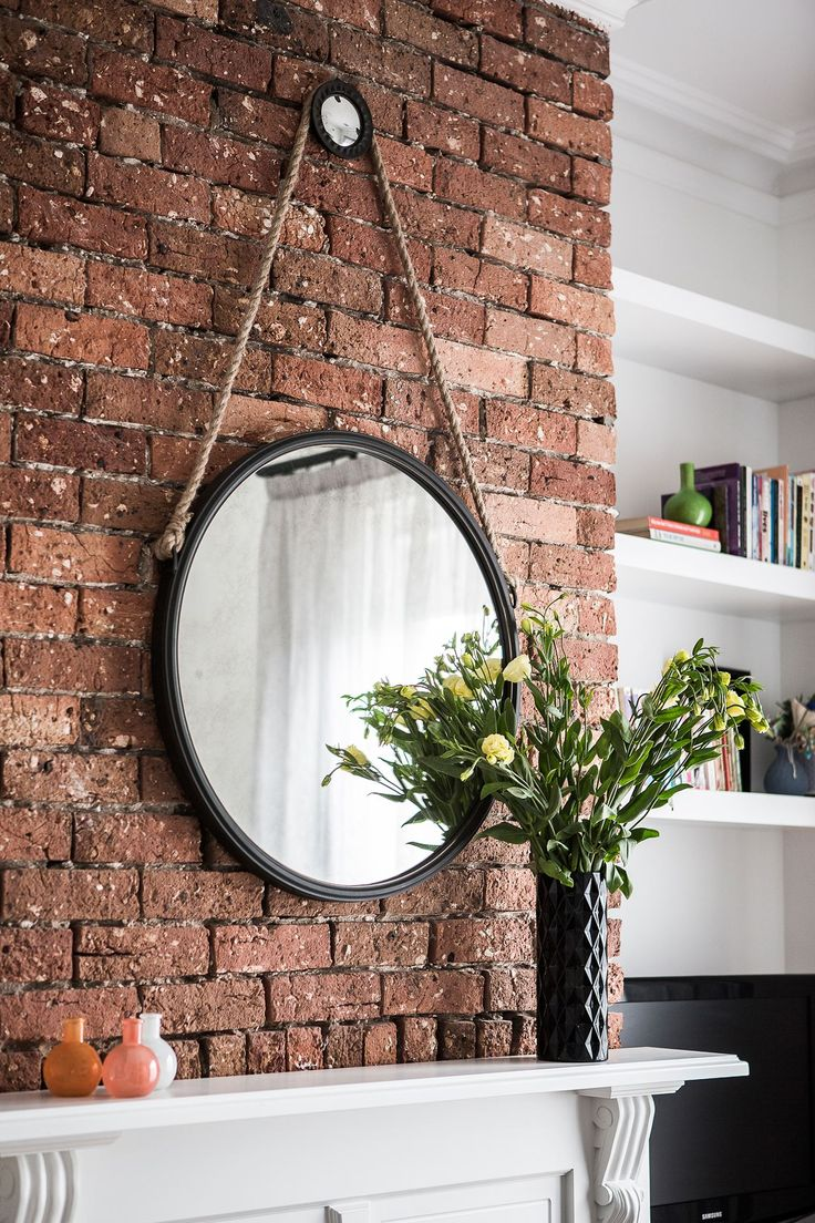 The smaller living room features a cosy fireplace with original exposed brickwork.