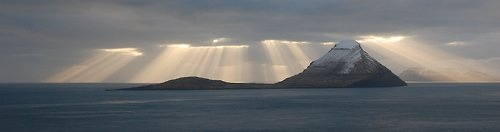 Ray's of light behind Koltur, Faroe Islands