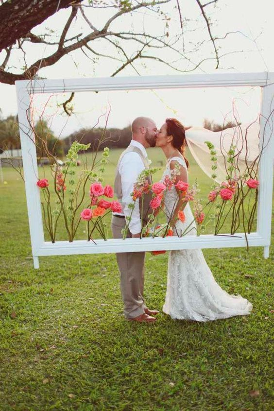 Crisp white picture frame filled with pink and orange flowers and greenery // http://www.deerpearlflowers.com/vintage-frames-wedding-decor-ideas/