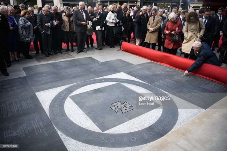 Guests and dignitaries look at the new monument listing the 64 servicemen who were awarded the Victoria Cross medal, after it was unveiled during a ceremony outside the Freemasons' Hall on April 25, 2017 in London, England. The monument commemorates the Freemason members who made up 108 of the 629 VC recipients from the First World War.