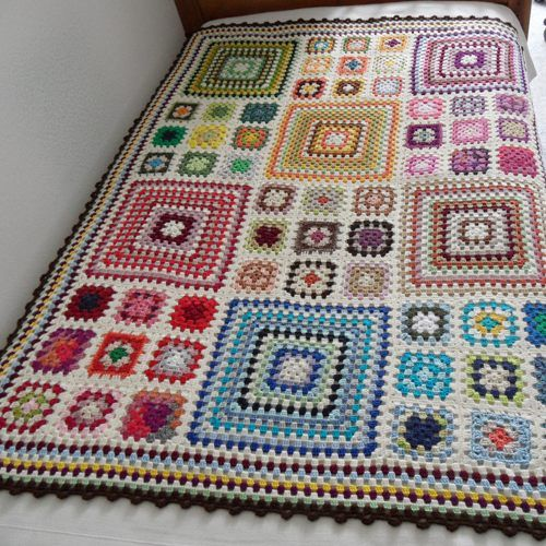 Crocheted Granny Square Blanket that was part of a charity auction held by Handmade Europe. The white pops the colors. 9 small squares equal one large to make this blanket exceptional. Note how the small squares take their colors from the large.