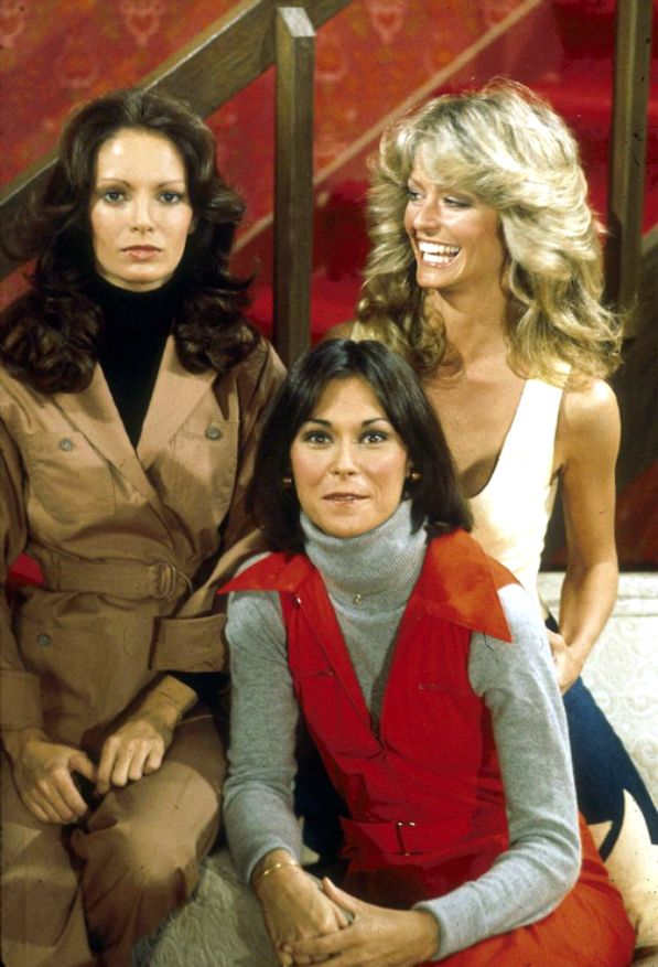 Farrah smiles at a very serious Jaclyn Smith. (Psst. That's Kate Jackson in front.)