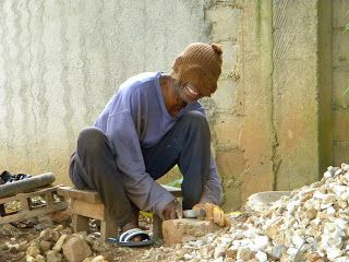 Papa Bamy, (blind brother) breaking rocks for gravel at a Kingdom Hall build in Guinea, West Africa.