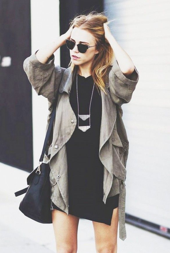 A black dress is worn with a olive green trench coat, black bag, silver layering necklace and sunglasses.