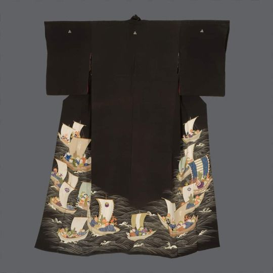 Geisha Hikizuri. Mid to late Meiji period (1880-1911), Japan. The Kimono Gallery. A soft chirimen-silk Geisha formal hikizuri featuring a fleet of auspicious treasure ships sailing on a frothy sea. Detailed yuzen-dyeing, with embroidery highlights and gold foil outlining.