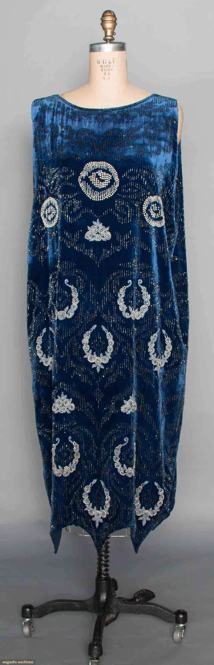 Beaded Blue Velvet Gown, C. 1920. Sapphire silk velvet, sleeveless, reverse scalloped hem, embellished w/ pearls & white beaded round blossoms above repeat patterns of pearls, crystal bead & blue rhinestone flower clusters & wreaths, bead motifs framed w/ blue carnival glass beaded ground, silk lining (hva)