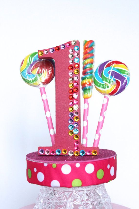 Over The Top Cake Topper offers a unique variety of unusual, custom cake toppers for any type of party, Wedding, Quinceanera, Sweet Sixteen, birthday, graduation, New Year's, Ball and all other celebrations and themes!  A colorful mix of lollipops surround a candy colored rhinestone number 4. The polka dot ribbon and glittery base to tie it all together. Perfect for your Candyland party.  Select from any number between 1-9 or letter between A - Z.  This cake topper is exactly what you need…