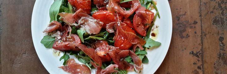 Salade van rucola, geroosterde tomaten en Parmaham (insalata di rucola, pomodori e prosciutto crudo). Deze salade van rucola, geroosterde tomaten en Parmaham laat zien wat het geheim is van een goed Italiaans gerecht. Zo simpel kan lekker eten zijn.