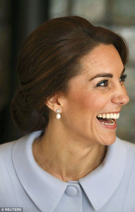 Kate shows off the pearl and diamond earrings loaned to her for today's visit by the Queen...