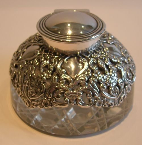 A wonderful heavy glass inkwell with a star cut base and covered in the most stunning cast sterling silver casing, beautiful pierced or reticulated detail. The domed hinged lid is in perfect working order. The silver is clearly hallmarked for London 1895, Victorian in era.