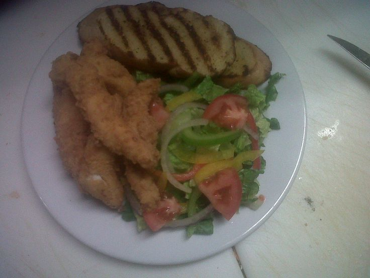 pan fried battered chicken breast served with a greens salad and grilled gralic bread