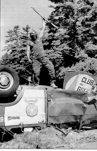Mohawk warrior stands atop an overturned Sûreté du Québec car as part of the barricade during the Oka Crisis, c. 1990The Oka Crisis was a land dispute between a group of Mohawk people and the town of Oka, Quebec, Canada which began on July 11, 1990 and lasted until September 26, 1990. One person died as a result. The dispute was the first well-publicized violent conflict between First Nations and the Canadian government in the late 20th century.