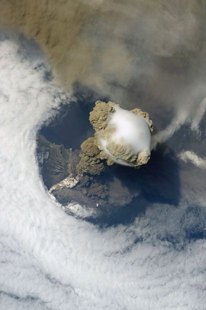 Pileus cloud above the Sarychev volcano as it erupts, Kuril Islands, Russia.  Pileus clouds, also called scarf or cap clouds, are small clouds that form on top of a bigger cloud. In this photo a pileus cloud (centre) has formed  above a cloud of volcanic ash from the Sarychev volcano. A large plume of smoke, steam and ash is erupting from the volcano while pyroclastic flow of denser ash descends the volcano sides. The picture was taken by astronauts aboard the International Space Station…