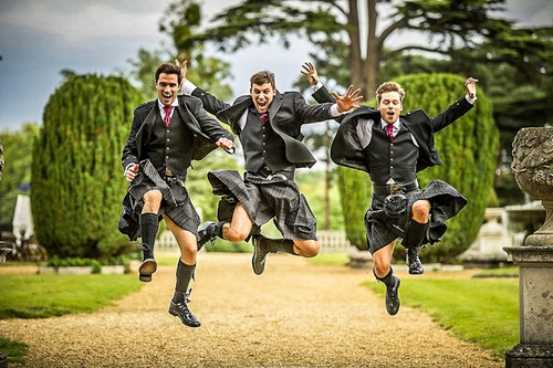 Jumping kilted groomsmen