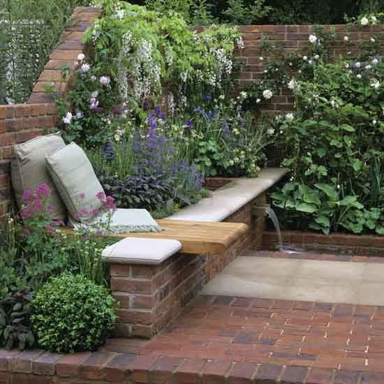 Brick walls and flooring creates a secret garden feel to this space. Grasses, shrubs and perennials fill the raised flowerbeds and give the garden a country feel. A bench with overhang, set into the flowerbed, provides the perfect spot to sit, and a water spout at the other end of the wall creates a calming atmosphere.