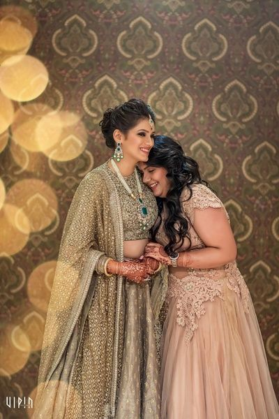 Sister of the Bride - Bride in a Sabyasachi Gold Lehenga and a Pearl, Diamond and Emerald Set and the Sister in a Light Pink Gown | WedMeGood  #wedmegood #pink #lehenga #indianbride #indianwedding #sisterofthebrideoutfit