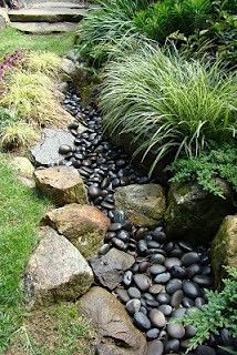 Dry River Bed Landscape Edging.  Dark rock gives the illusion of water.  Plant grasses and ferns along edge of landscaping.  Add dark river rocks to give the illusion of water and follow with larger rocks like you would find along a river bed.  Great idea!!  Love the natural look of this edging. May be a pretty solution for my drainage problems