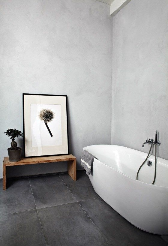 Minimalist bathroom, large black tile, concrete walls, modern freestanding tub, bench in bathroom, modern bathroom