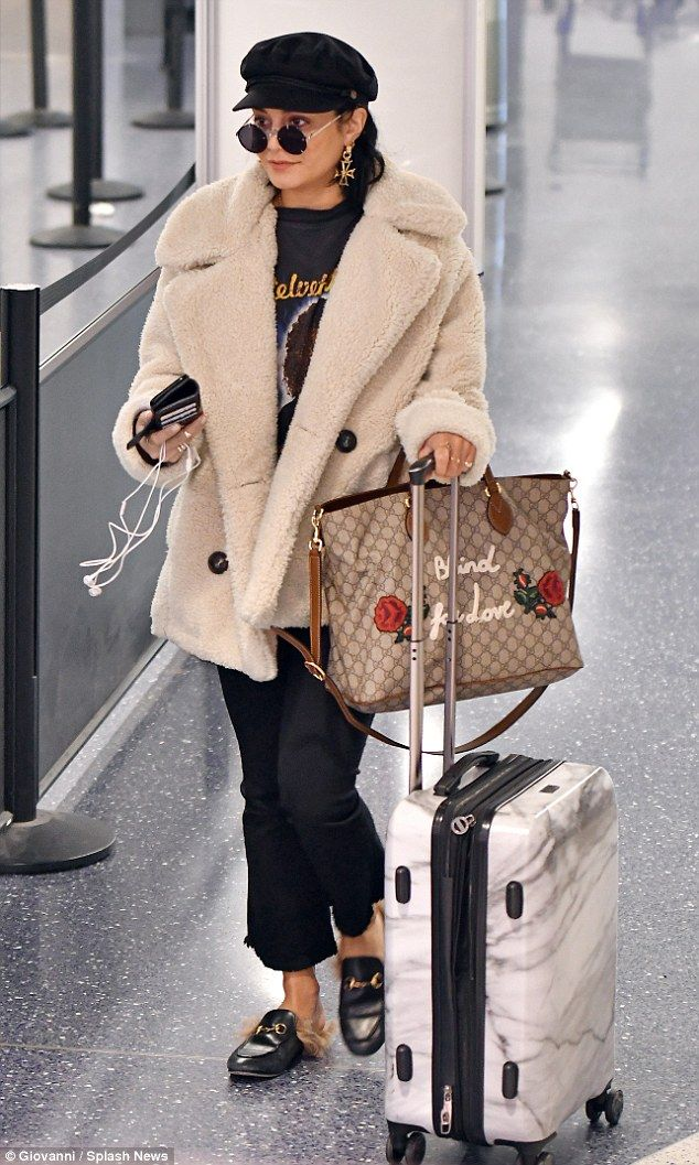 Furry: Vanessa Hudgens put on a fashion show as she arrived at LAX Tuesday wearing a blac...